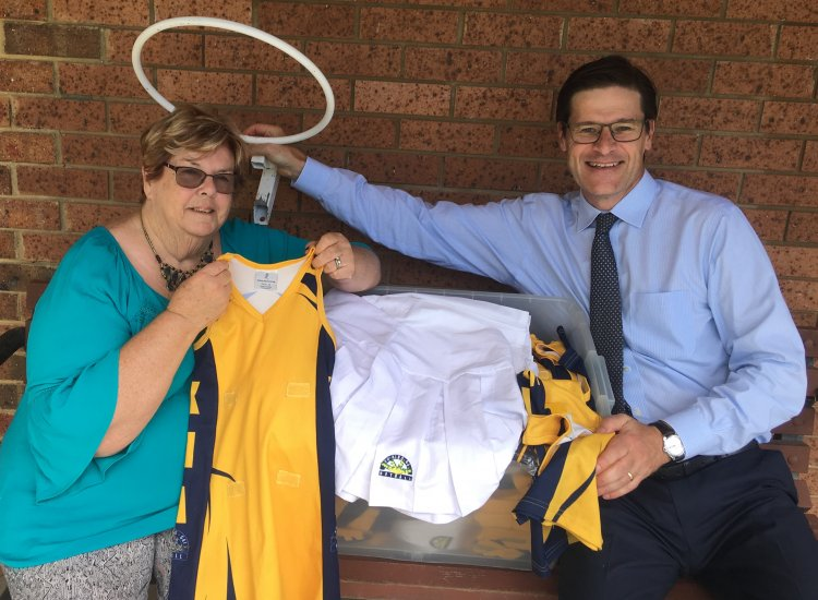 'Saint' Brenda Williams handing Jonathan O'Dea MP some of the netball uniforms donated for needy children in The Solomons